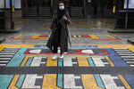 A woman walks over a pedestrian crossing, part of a public artwork by French artist Camille Walala, in London, Tuesday, Oct. 27, 2020. The British government is sticking to its strategy of tiered, regional restrictions to combat COVID-19 amid mounting political and scientific pressure for stronger nationwide measures to prevent the pandemic from spiralling out of control. (AP Photo/Kirsty Wigglesworth)
