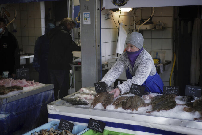 FILE - In this Thursday, Dec. 10, 2020 file photo, a fish seller arranges her stall at the market of the port of Boulogne-sur-Mer, northern France. The European Council adopted Tuesday, Sept. 28, 2021 a euro 5 billion (US dollar 5.8 billion) reserve aimed at helping businesses tackle the short-term negative effects of Brexit. Britain's departure has affected many parts of the EU economy, with the fishing sector particularly at risk. According to the European Commission, EU fisheries face a 25 percent reduction of their catch value in UK waters. (AP Photo/Thibault Camus, File)