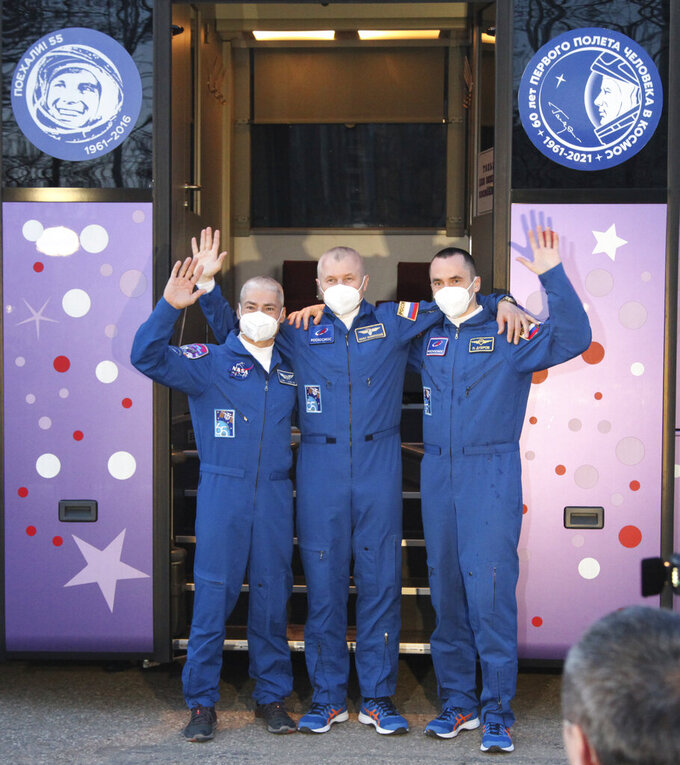In this photo released by the Roscosmos Space Agency, from left, U.S. astronaut Mark Vande Hei, Russian cosmonauts Oleg Novitsky and Pyotr Dubrov, members of the main crew to the International Space Station (ISS), waves near a bus with portraits of the first cosmonaut Yuri Gagarin prior to the launch at the Russian leased Baikonur cosmodrome, Kazakhstan, Friday, April 9, 2021. A Russian-U.S. trio of space travelers have launched successfully, heading for the International Space Station. NASA astronaut Mark Vande Hei and Russian cosmonauts Oleg Novitskiy and Pyotr Dubrov blasted off as scheduled at 12:42 p.m. (0742 GMT, 3:42 a.m. EDT) Friday aboard the Soyuz MS-18 spacecraft from the Russia-leased Baikonur launch facility in Kazakhstan. (Roscosmos Space Agency via AP)