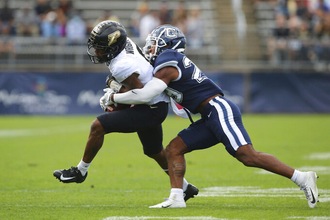 Purdue wide receiver Milton Wright (0) is tackled by Connecticut linebacker Jordan Morrison (29) during an NCAA football game on Saturday, Sept. 11, 2021, in East Hartford, Conn. (AP Photo/Stew Milne)