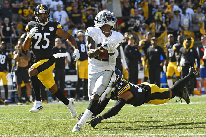 Las Vegas Raiders wide receiver Henry Ruggs III (11) hauls in a pass from quarterback Derek Carr between defenders Pittsburgh Steelers free safety Minkah Fitzpatrick (39) and cornerback Ahkello Witherspoon (25) and takes it for a touchdown during the second half of an NFL football game in Pittsburgh, Sunday, Sept. 19, 2021. The Raiders won 26-17. (AP Photo/Don Wright)
