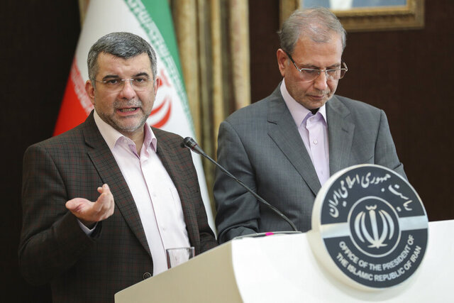 In this Monday Feb. 24, 2020 photo, released by the official website of the office of the Iranian Presidency, the head of Iran's counter-coronavirus task force, Iraj Harirchi, left, speaks at a press briefing with government spokesman Ali Rabiei, in Tehran, Iran. Harirchi, has tested positive for the virus himself, authorities announced Tuesday, amid concerns the outbreak may be far wider than officially acknowledged. The announcement regarding Harirchi came after the news conference seeking to minimize the danger posed by the outbreak. (Iranian Presidency Office via AP)