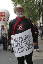 A retired man holds a placard which reads