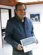 Associated Press reporter Cesar Garcia poses for a photo as he marks his 20 year anniversary with the AP at his office in Bogota, Colombia, Friday, May 31, 2019. Garcia, a veteran reporter who ventured across Colombia to tell the story of the nation's armed conflict, has died at age 61. (AP Photo/Fernando Vergara)