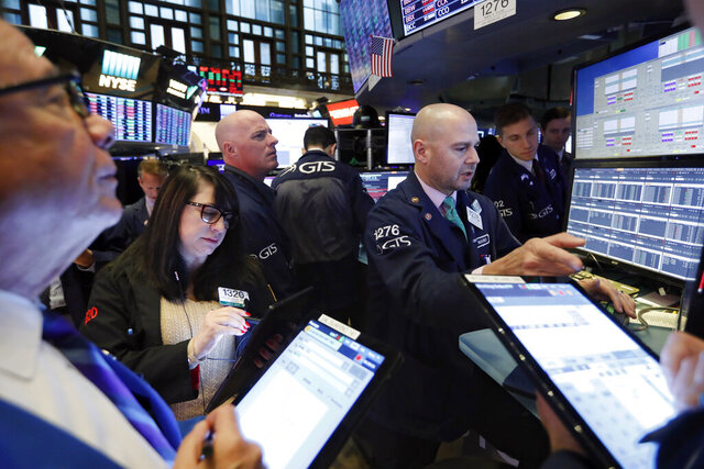 FILE - In this Nov. 20, 2019, file photo specialist Mario Picone, right, works with traders at his post on the floor of the New York Stock Exchange. The U.S. stock market opens at 9:30 a.m. EST on Tuesday, Nov 26. (AP Photo/Richard Drew, File)