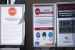 Signs about COVID-19 stand outside a door to enter the Pat Bowlen Fieldhouse during an NFL football practice Wednesday, Oct. 28, 2020, at the headquarters of the Denver Broncos in Englewood, Colo. The Broncos' offensive line coach, Mike Munchak, did not attend the practice because of COVID-19 reasons. (AP Photo/David Zalubowski)