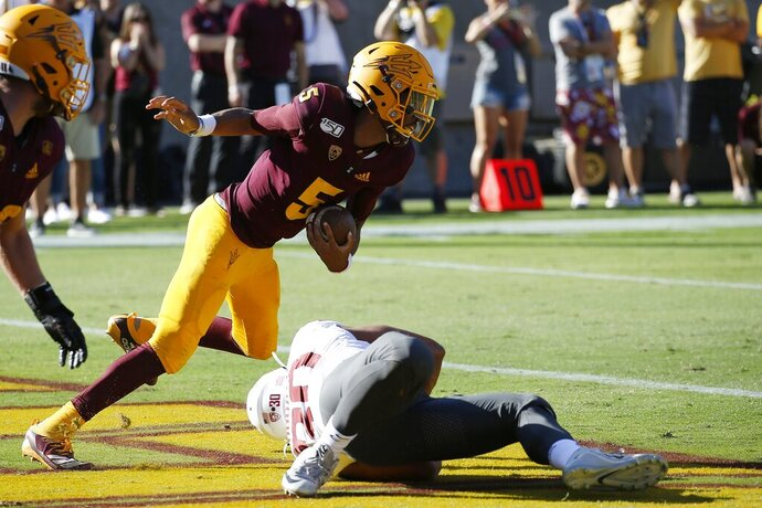 Arizona State quarterback Jayden Daniels (5) eludes Washington State defensive lineman Nnamdi Oguayo (30) to avoid a safety in the end zone during the second half of an NCAA college football game Saturday, Oct. 12, 2019, in Tempe, Ariz. (AP Photo/Ross D. Franklin)