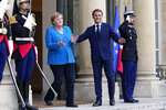 France's President Emmanuel Macron, right, welcomes German Chancellor Angela Merkel prior to a meeting at the Elysee Palace, in Paris, Thursday, Sept. 16, 2021. (AP Photo/Michel Euler)