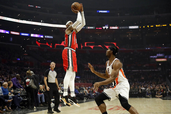 Portland Trail Blazers' Carmelo Anthony, left, shoots over Los Angeles Clippers' Maurice Harkless during the first half of an NBA basketball game Tuesday, Dec. 3, 2019, in Los Angeles. (AP Photo/Marcio Jose Sanchez)