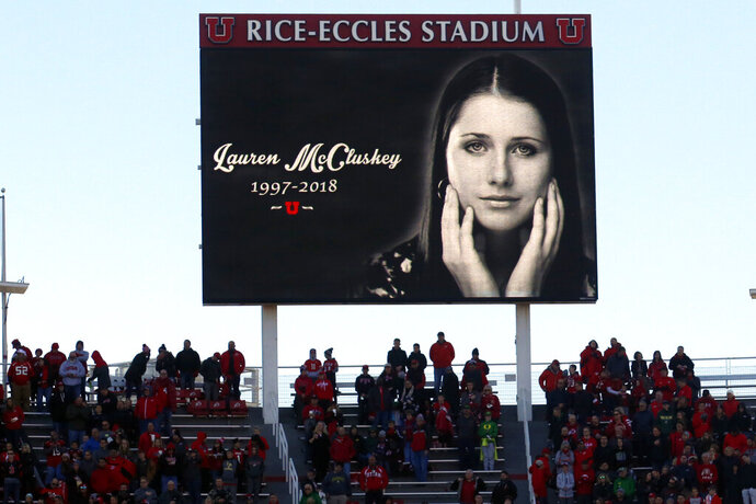 FILE - In this Nov. 10, 2018, file photo, a photograph of University of Utah student and track athlete Lauren McCluskey, who was fatally shot on campus, is projected on the video board before the start of an NCAA college football game between Oregon and Utah in Salt Lake City. An investigation found Wednesday, Aug. 5, 2020, that a group of University of Utah police officers made inappropriate comments about explicit photos of McCluskey, who had submitted the pictures as evidence in an extortion case shortly before her shooting death. The findings came after the Salt Lake Tribune unearthed allegations that an officer had bragged about having the images of McCluskey before her 2018 slaying. (AP Photo/Rick Bowmer, File)