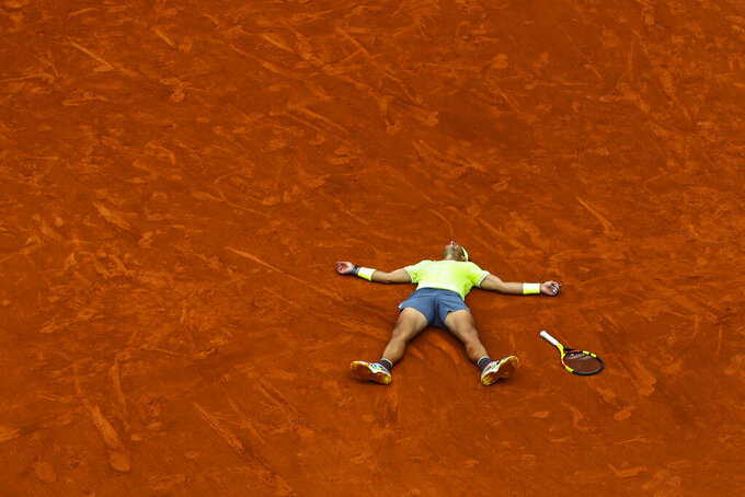 Spain's Rafael Nadal celebrates his record 12th French Open tennis tournament title after winning his men's final match against Austria's Dominic Thiem in four sets, 6-3, 5-7, 6-1, 6-1, at the Roland Garros stadium in Paris, June 9, 2019. (AP Photo/Pavel Golovkin)