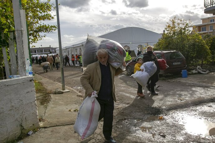 People carry clothes and other supplies distributed by authorities in Thumane, western Albania, Friday, Nov. 29, 2019. The operation to find survivors and recover bodies from Albania's deadly earthquake was winding down Friday as the death toll climbed to 49. (AP Photo/Visar Kryeziu)
