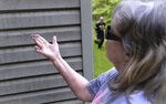 Sandy Stewart wipes dust from the side of her house in Eunice, W.V., May 18, 2021. She and her husband Charles live closest to the coal mine nearby. (Chris Dorst/ Charleston Gazette-Mail via AP)