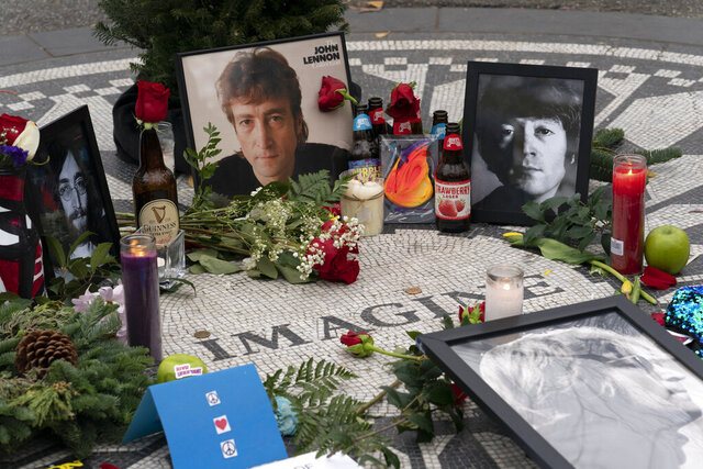 Photos, flowers, and candles have been left at Strawberry Fields in New York's Central Park to remember John Lennon, Tuesday, Dec. 8, 2020. The rock star and former Beatle was shot to death outside his New York City apartment building by a fan on Dec. 8, 1980. (AP Photo/Mark Lennihan)