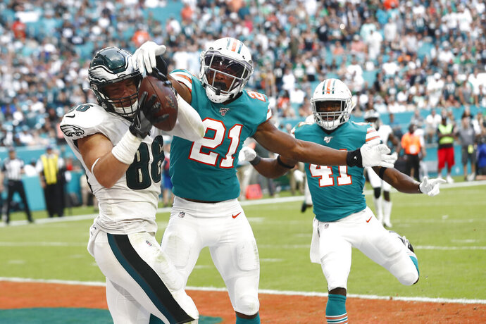 Philadelphia Eagles tight end Zach Ertz (86) attempts to hold onto a pass in the engine as Miami Dolphins cornerback Eric Rowe (21) defends, during the second half at an NFL football game, Sunday, Dec. 1, 2019, in Miami Gardens, Fla. Ertz dropped the football. (AP Photo/Brynn Anderson)