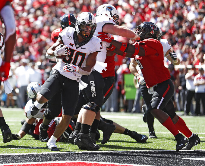 Oklahoma State's Chuba Hubbard (30) scores a touchdown during the second half of an NCAA college football game against Texas Tech, Saturday, Oct. 5, 2019, in Lubbock, Texas. (AP Photo/Brad Tollefson)