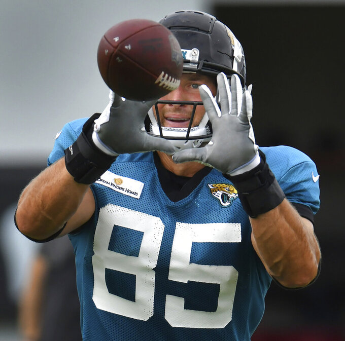 Jacksonville Jaguars' Tim Tebow prepares to catch a short pass from quarterback Gardner Minshew II during an NFL football training camp in Jacksonville, Fla., Tuesday, Aug. 3, 2021. (Bob Self/The Florida Times-Union via AP)