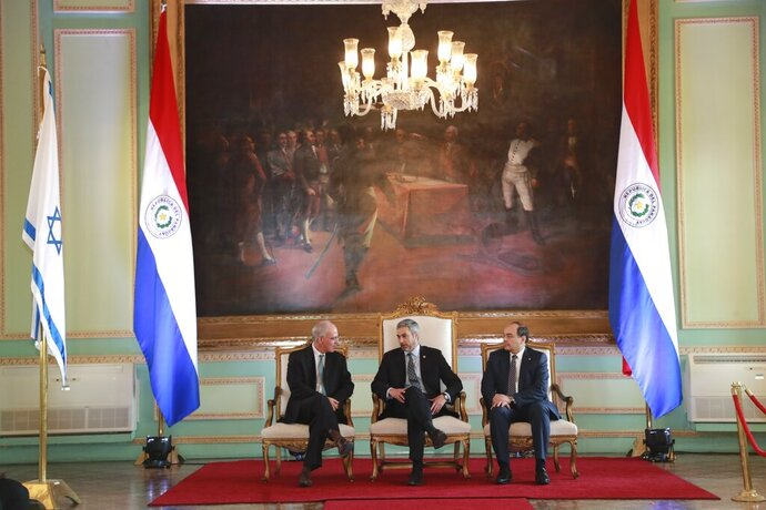 In this hand out picture released by Paraguay's Government Press Office, President Mario Abdo Benitez, center, talks to Israel's new ambassador to Paraguay, Yoed Magen, left, as Foreign Minister Antonio Rivas Palacios, right, listens, during official ceremony, at Lopez Palace, Asuncion, Paraguay, Wednesday, Aug. 21, 2019. (Anibal Ovelar/Paraguay's Government Press Office via AP)