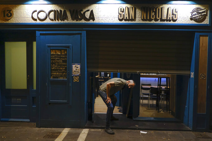 A worker prepares to close a bar in Pamplona, northern Spain, Thursday, March 31, 2021, as new measures against the coronavirus began in the Navarra province and other regions of the country where all bars without terraces will be closing to prevent the spread COVI-19. (AP Photo/Alvaro Barrientos)