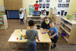 In this May 27, 2020, photo, teachers Jana Blair, right, and Aaron Rainboth, upper-center, wear masks as they work with kids at the Frederickson KinderCare daycare center, in Tacoma, Wash. In a world weary of the coronavirus, many working parents with young children are now struggling with the decision on when or how they'll be comfortable returning to their child care providers. Frederickson KinderCare, which has been open throughout the pandemic to care for children of essential workers, removed carpets and spaced out tables and chairs as part of their measures to control the spread of the coronavirus. (AP Photo/Ted S. Warren)