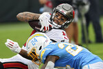 Tampa Bay Buccaneers wide receiver Mike Evans (13) winces as he is hit by Los Angeles Chargers free safety Nasir Adderley (24) after making catch during the second half of an NFL football game Sunday, Oct. 4, 2020, in Tampa, Fla. (AP Photo/Mark LoMoglio)