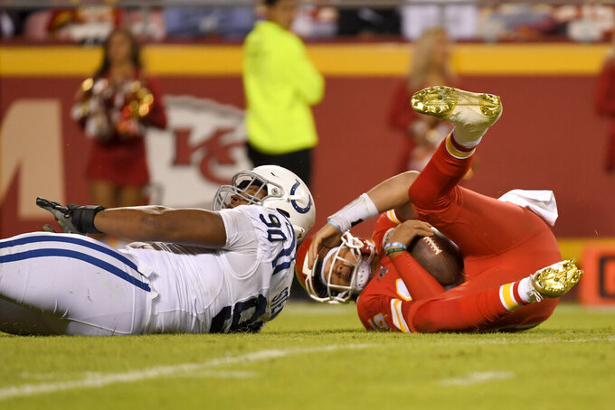 Kansas City Chiefs quarterback Patrick Mahomes, right, tumbles after a sack by Indianapolis Colts defensive tackle Grover Stewart (90) during the second half of an NFL football game in Kansas City, Mo., Sunday, Oct. 6, 2019. (AP Photo/Reed Hoffmann)