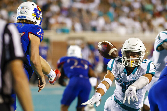 Coastal Carolina safety Alex Spillum, right, blocks a punt by Kansas' Reis Vernon (24) during the first half of an NCAA college football game in Conway, S.C., Friday, Sept. 10, 2021. Spillum recovered the ball and scored a touchdown. (AP Photo/Nell Redmond)