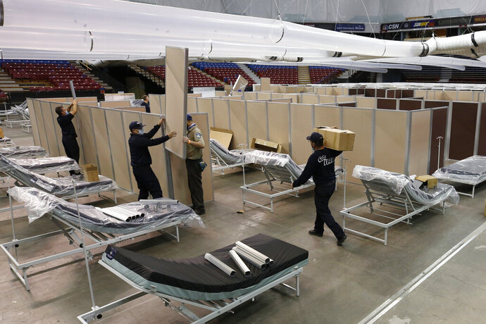 FILE - In this April 18, 2020, file photo, partitions are installed between beds as work is performed to turn Sleep Train Arena in Sacramento, Calif., into a 400-bed emergency field hospital to help deal with the coronavirus outbreak. When California was anticipating a spring surge in coronavirus cases it turned an old NBA arena and practice facility into a field hospital prepared to take hundreds of patients. They were told to expect 30 to 60 patients within the first few days, but only nine arrived over the next 10 weeks. (AP Photo/Rich Pedroncelli, File)