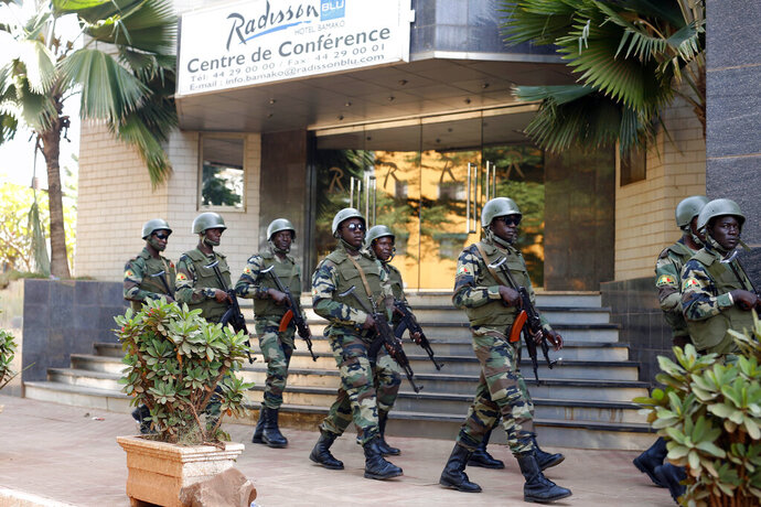 FILE- In this Saturday, Nov. 21, 2015 file photo, soldiers from the presidential guard patrol outside the Radisson Blu hotel in Bamako after it was attacked by Islamic extremists armed with guns and grenades. Islamic extremists have displaced half a million people this year in the border area between Burkina Faso and Mali as their threat continues to spread in West Africa's Sahel region. The fighters linked to al-Qaida and the Islamic State group are exploiting military and government weaknesses as well as local grievances. A regional counterterror force has failed to stop the attacks and has become a target itself. (AP Photo/Jerome Delay, File)