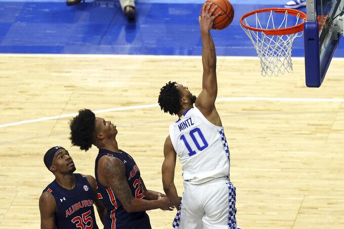 Kentucky's Davion Mintz (10) dunks in front of Auburn's Devan Cambridge (35) and Allen Flanigan during the second half of an NCAA college basketball game in Lexington, Ky., Saturday, Feb. 13, 2021. Kentucky won 82-80. (AP Photo/James Crisp)