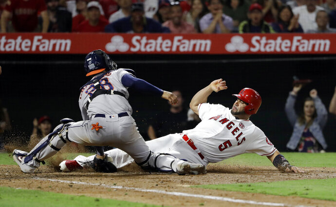 Los Angeles Angels' Albert Pujols, right, scores past Houston Astros catcher Robinson Chirinos after a double by Kevan Smith and a throwing error by Astros second baseman Jose Altuve during the seventh inning of a baseball game, Monday, July 15, 2019, in Anaheim, Calif. (AP Photo/Marcio Jose Sanchez)