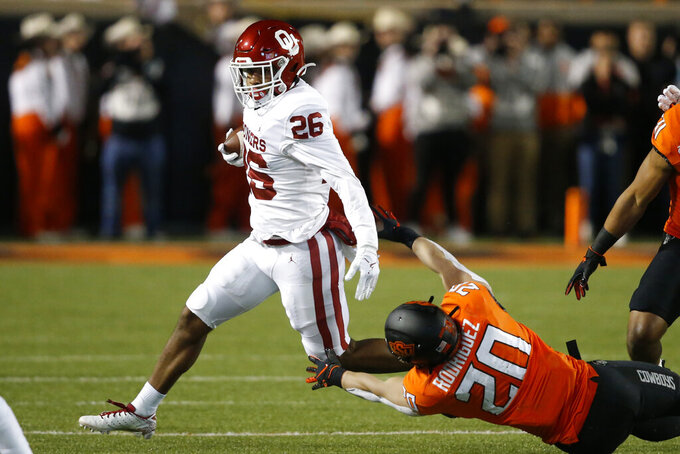 Oklahoma running back Kennedy Brooks (26) avoids a tackle by Oklahoma State safety Malcolm Rodriguez (20) in the fist half of an NCAA college football game in Stillwater, Okla., Saturday, Nov. 30, 2019. (AP Photo/Sue Ogrocki)