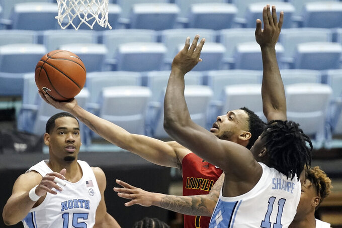 Louisville guard Carlik Jones (1) drives to the basket while North Carolina forwards Day'Ron Sharpe (11) and Garrison Brooks (15) defend during the second half of an NCAA college basketball game in Chapel Hill, N.C., Saturday, Feb. 20, 2021. (AP Photo/Gerry Broome)