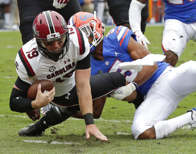 South Carolina quarterback Jake Bentley (19) is stopped by Florida defensive back CJ Henderson, right, during the first half of an NCAA college football game, Saturday, Nov. 10, 2018, in Gainesville, Fla. (AP Photo/John Raoux)