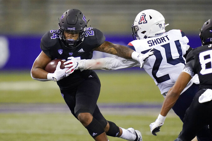 Washington's Kamari Pleasant, left, pushes away Arizona's Rhedi Short on Pleasant's 21-yard touchdown run during the second half of an NCAA college football game Saturday, Nov. 21, 2020, in Seattle. (AP Photo/Elaine Thompson)