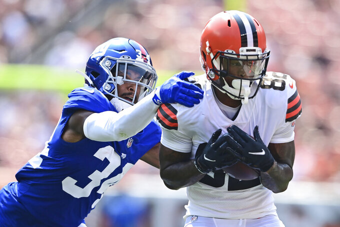 Cleveland Browns wide receiver Rashard Higgins (82) catches a pass under pressure from New York Giants running back Sandro Platzgummer (34) during the first half of an NFL football game, Sunday, Aug. 22, 2021, in Cleveland. (AP Photo/David Dermer)