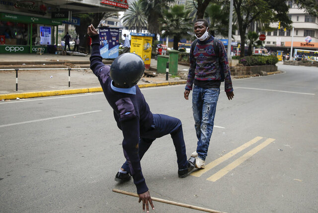 A Kenyan policeman running to arrest a protester slips and falls over just as he reaches him, before proceeding to arrest him, during a demonstration in downtown Nairobi, Kenya Tuesday, July 7, 2020. Kenyan police have fired tear gas and detained scores of protesters who were demanding an end to police brutality. (AP Photo/Brian Inganga)