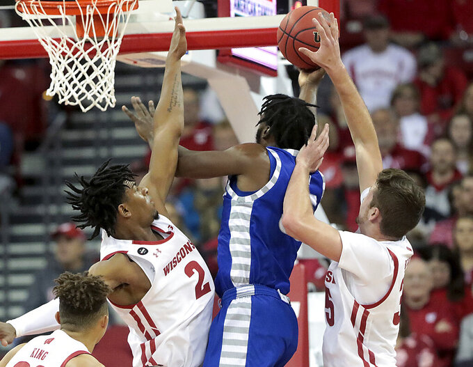 Wisconsin forwards Aleem Ford (2) and Nate Reuvers, right, contest the shot of Eastern Illinois guard George Dixon, second from right, during the first half of an NCAA college basketball game in Madison, Wis., Friday, Nov. 8, 2019. (John Hart/Wisconsin State Journal via AP)