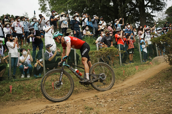 Fans watch from a hillside as Nino Schurter of Switzerland competes during the men's cross country mountain bike competition at the 2020 Summer Olympics, Monday, July 26, 2021, in Izu, Japan. (AP Photo/Thibault Camus)