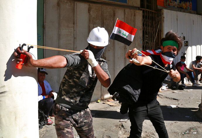 Anti-government protesters throw stones at security forces during clashes in the al-Rasheed street in Baghdad, Iraq, Friday, Nov. 8, 2019. The demonstrators complain of widespread corruption, lack of job opportunities and poor basic services, including regular power cuts despite Iraq's vast oil reserves. They have snubbed limited economic reforms proposed by the government, calling for it to resign. (AP Photo/Khalid Mohammed)