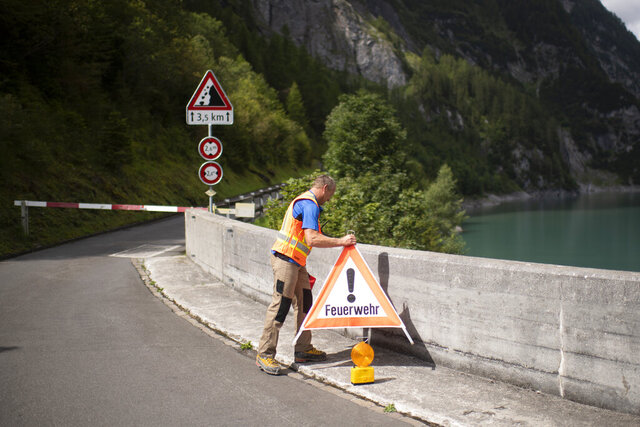 A road is blocked block on the Gigerwald reservoir dam in Vaettis, Switzerland, Thursday, August 13, 2020. The road is blocked due to a ongoing search-and-rescue mission after a canyoning accident in the region yesterday night. Swiss authorities say three Spanish tourists on a canyoning tour have died and one is missing after a heavy storm. (Gian Ehrenzeller/Keystone via AP)