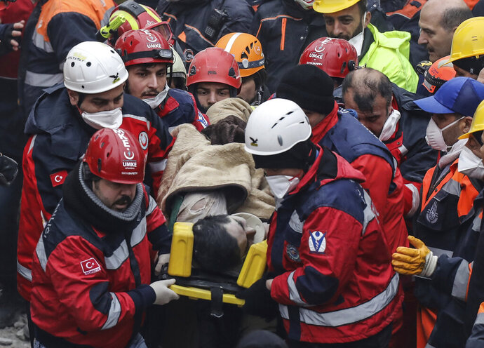Turkish rescue workers carry a 16-year-old boy after they pulled him out from the rubble of an eight-story building which collapsed two days earlier in Istanbul, Friday, Feb. 8, 2019. (AP Photo/Emrah Gurel)