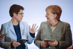 German Chancellor Angela Merkel, right, and CDU party chairwoman Annegret Kramp-Karrenbauer use tablet computers as they attend a Christian Social Union party board meeting at the eve of a party convention in Leipzig, Wednesday, Nov. 20, 2019. (AP Photo/Markus Schreiber)