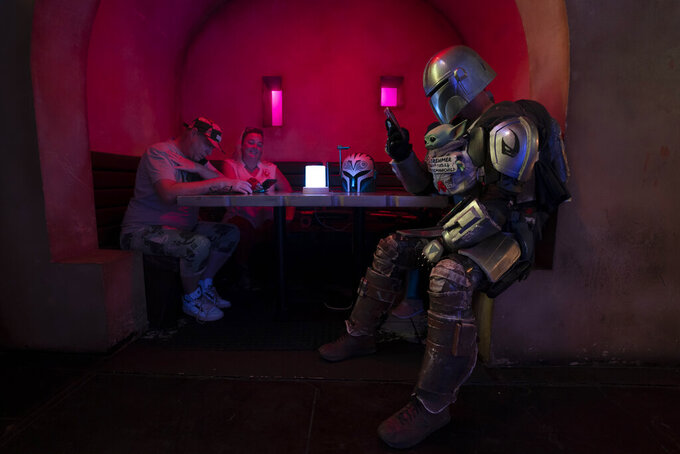 Dressed in a Star Wars costume, Tim Brehmer, right, sits in a booth as customers gather to celebrate the Star Wars Day at Scum and Villainy Cantina, a geek bar located on Hollywood Blvd, in Los Angeles, Tuesday, May 4, 2021. California has the lowest infection rate in the country. Los Angeles County, which is home to a quarter of the state's nearly 40 million people and has endured a disproportionate number of the state's 60,000 deaths, didn't record a single COVID-19 death Sunday or Monday, which was likely due to incomplete weekend reporting but still noteworthy. (AP Photo/Jae C. Hong)