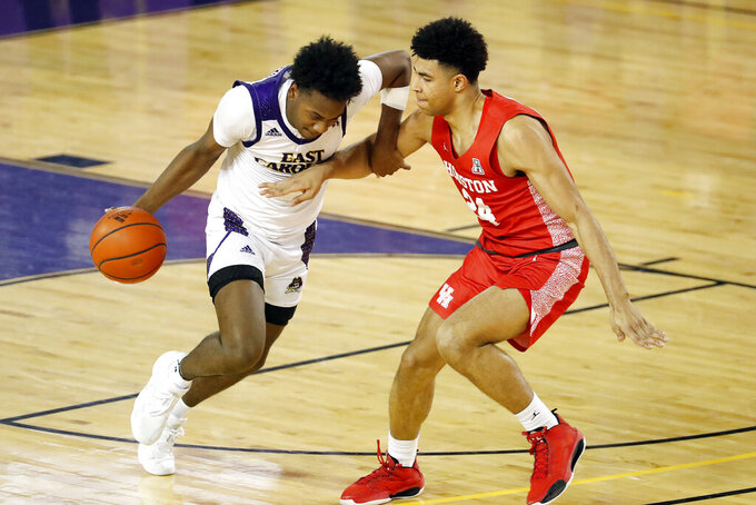 East Carolina's Tristen Newton (2) tries to drive the ball past Houston's Quentin Grimes (24) during the second half of an NCAA college basketball game in Greenville, N.C., Wednesday, Feb. 3, 2021. (AP Photo/Karl B DeBlaker)