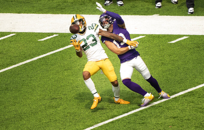 Green Bay Packers defender Jaire Alexander, left, intercepts a pass intended for Minnesota Vikings wide receiver Adam Thielen, right, in the second quarter of an NFL football game Sunday, Sept. 13, 2020, in Minneapolis.  (Jerry Holt/Star Tribune via AP)