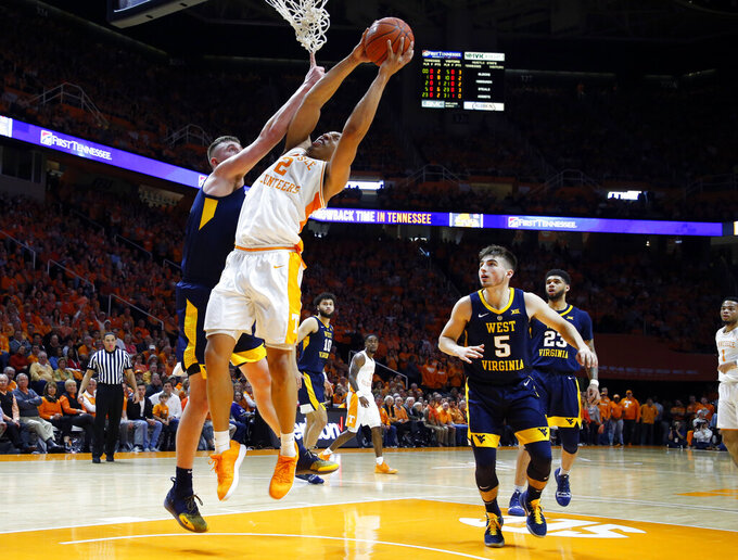 Tennessee forward Grant Williams (2) is fouled by West Virginia forward Logan Routt (31) as he goes for a shot in the first half of an NCAA college basketball game Saturday, Jan. 26, 2019, in Knoxville, Tenn. (AP Photo/Wade Payne)
