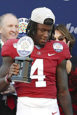 Alabama wide receiver Jerry Jeudy holds up the trophy after he was named MVP of the Citrus Bowl after defeating Michigan in an NCAA college football game, Wednesday, Jan. 1, 2020, in Orlando, Fla. (AP Photo/John Raoux)