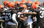 Cleveland Browns running back Nick Chubb, center, is stopped by the defense during practice at the NFL football team's training camp facility, Saturday, July 27, 2019, in Berea, Ohio. (AP Photo/Tony Dejak)