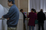 Investors chat with each others as they monitor stock prices at a brokerage house in Beijing, Wednesday, Oct. 23, 2019. Asian stock markets followed Wall Street lower Wednesday after major companies reported mixed earnings and an EU leader said he would recommend the trade bloc allow Britain to delay its departure. (AP Photo/Andy Wong)